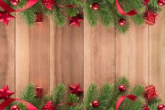 Kerstboombladeren met rode ornamenten op houten achtergrond Stock Fotografie