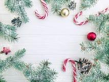 Kerstboomtak, de pineconewinter, het feestelijke suikergoed van de groetsneeuw op een witte houten achtergrondkaartbal stock afbeeldingen