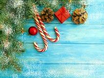 Kerstboomtak, de winter, het seizoengebonden suikergoed van de sneeuwgrens op een blauwe houten achtergrondkaartbal stock afbeeldingen