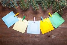 Kerstboomtak en gekleurde wasknijpers met fotokaders Stock Fotografie