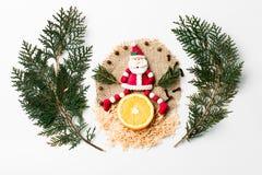 Kerstboomtak, Santa New Year-decoratie, plak van citroen op wit Creatief concept, ruimte voor tekst Royalty-vrije Stock Fotografie