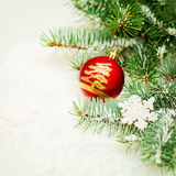 Kerstboomtakje en het Rode Decor van Balkerstmis op Sneeuw Royalty-vrije Stock Afbeelding