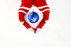Kerstkaart, handschoenen op handen die blauwe bal met snowflak houden Royalty-vrije Stock Foto