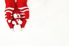 Kerstkaart, handschoenen op handen die een sneeuwman houden die op a wordt geïsoleerd Royalty-vrije Stock Fotografie