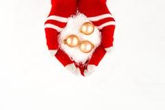 Kerstkaart, handschoenen op handen die gouden bal drie met sno houden Stock Afbeelding