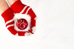 Kerstkaart, handschoenen op handen die rode bal met sneeuwvlokken houden Stock Foto's