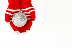 Kerstkaart, handschoenen op handen die zilveren bal geïsoleerd houden  Stock Afbeelding