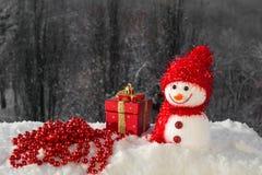 Kerstkaart met een leuk sneeuwman, een Kerstmisstuk speelgoed en parels Royalty-vrije Stock Foto's