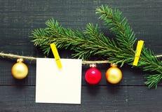 Kerstkaart met Kerstboomdecoratie en een sparrentak op een draad Stock Fotografie
