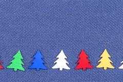 Kerstkaart met kleurrijke Kerstbomen op een achtergrond van blauwe stof Stock Fotografie