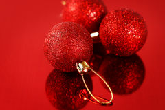 Kerstkaart met rode snuisterijen en fonkelingen Stock Afbeelding