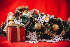 Kerstkaart met sparrentak met gouden snuisterijen, slingers en uitstekende sneeuwvlokken op een rode achtergrond wordt verfraaid  Royalty-vrije Stock Foto's