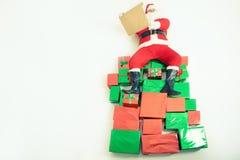 Kerstman die bij grote giftvakjes zitten en wenslijst lezen Stock Afbeelding