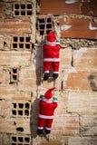Kerstman die een grungemuur beklimmen stock fotografie
