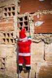 Kerstman die een grungemuur beklimmen royalty-vrije stock foto