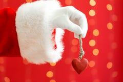Kerstman die een Kerstmishart houden stock foto
