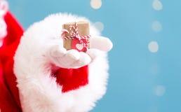 Kerstman die een kleine Kerstmisgift houden royalty-vrije stock foto