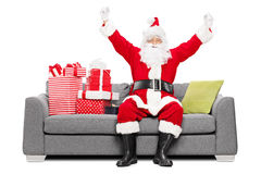 Kerstman die geluk gezet op bank met giften gesturing Stock Foto