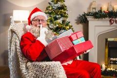 Kerstman die met giftdozen op stoel met vinger op lippen in woonkamer de zitten Stock Fotografie