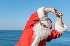 Kerstman die oefeningen op de oceaan doen Traditionele rode uitrusting en het ontspannen op het strand stock foto