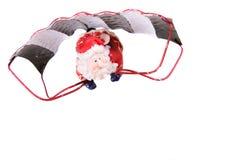 Kerstman die op een valscherm vliegen stock fotografie