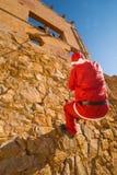 Kerstman die proberen te beklimmen Stock Foto's