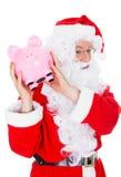Kerstman die spaarvarken houden Stock Afbeeldingen