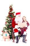 Kerstman die verhaal voor leuk meisje lezen royalty-vrije stock afbeeldingen