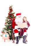 Kerstman die verhaal voor leuk meisje lezen royalty-vrije stock foto's