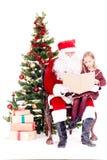 Kerstman die verhaal voor leuk meisje lezen royalty-vrije stock afbeelding