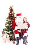 Kerstman die verhaal voor leuk meisje lezen stock afbeeldingen