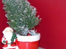 Kerstman die zich door een Kerstmisboom bevinden stock foto's