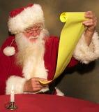 Kerstman die Zijn Lijst controleren Stock Fotografie