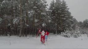Kerstman in een rode laag met een zak en een witte baard en een jonge kleindochter in het hout in de winter stock footage