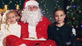Kerstman en jonge geitjes dichtbij de verfraaide Kerstboom Wensenlijst stock footage
