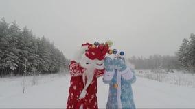 Kerstman en kleindochter op aard in de winter in het bos die op Kerstmisballen werpen stock footage