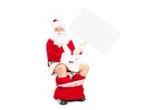 Kerstman gezet op toilet en holding een lege banner Stock Foto's