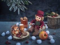 Kerstman Klaus, hemel, vorst, zak Het speelgoed de houtvester en de egel zit bij de stompen en eet royalty-vrije stock afbeelding