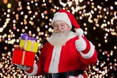 Kerstman met giften die duim tonen Stock Fotografie