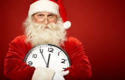 Kerstman met klok Stock Afbeeldingen