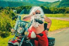Kerstman op een motorfiets stock foto's
