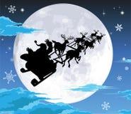 Kerstman in sleesilhouet tegen volle maan Stock Afbeeldingen