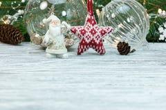 Kerstmanbeeldje, Kerstmisballen en sparrentak met lichten stock afbeeldingen