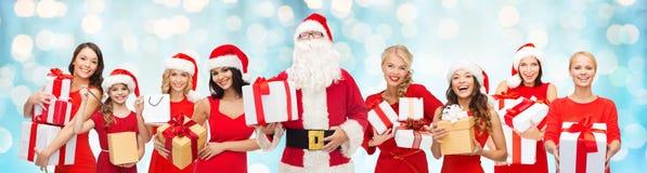 Kerstmancalaus en gelukkige vrouwen met giftdozen Stock Fotografie