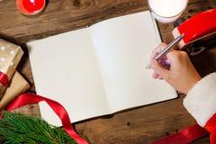 Kerstmanhand die op Kerstmisboek schrijven Stock Afbeeldingen