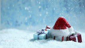 Kerstmanhoed en giften in sneeuw stock footage