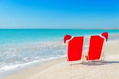 Kerstmanhoed op chaise-longues bij wit zandstrand tegen het overzees Stock Afbeeldingen
