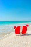 Kerstmanhoed op chaise-longues bij wit zandstrand tegen het overzees Royalty-vrije Stock Foto