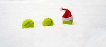 Kerstmanhoed op tennisbal op witte sneeuwachtergrond Kerstmis en Nieuw jaarconcept met tennisballen Sluit omhoog, sportlevensstij stock foto's