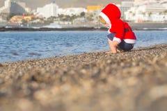 Kerstmanjongen bij het water van het zandstrand Royalty-vrije Stock Afbeelding